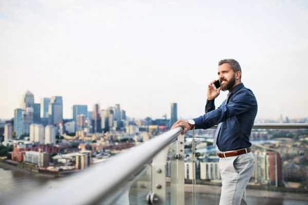 A portrait of businessman with smartphone standing against London rooftop view panorama, making a phone call. Copy space.